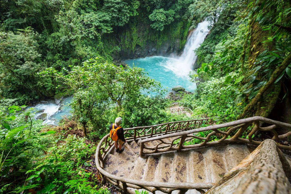 Person descending stairs to waterfall in costa rica
