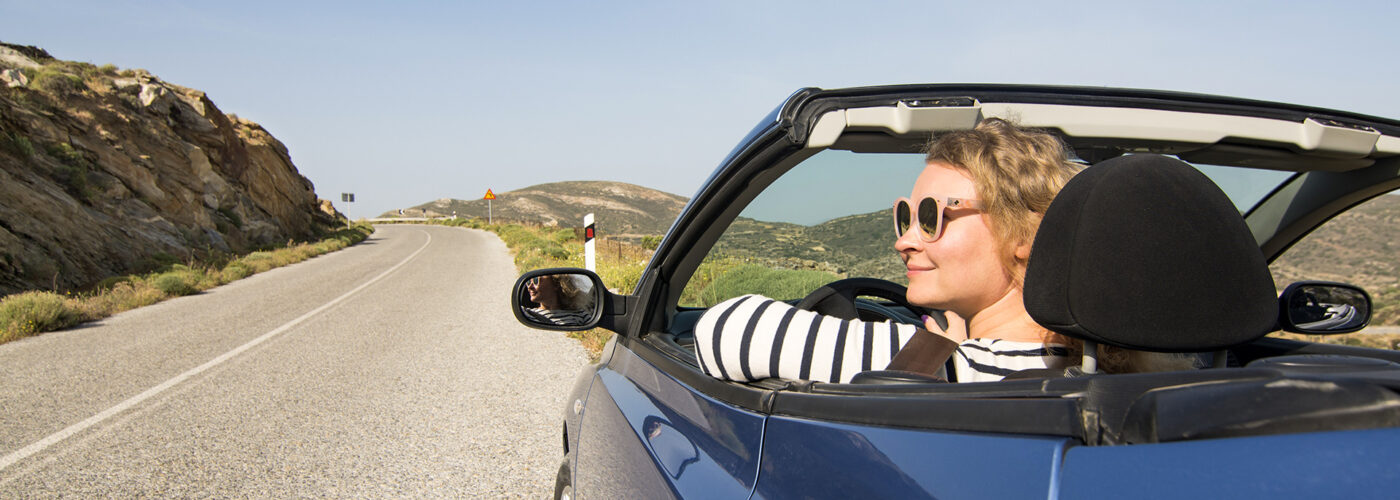 Young blonde woman driving in convertible blue car without roof on mountain road in Naxos island, Greece.
