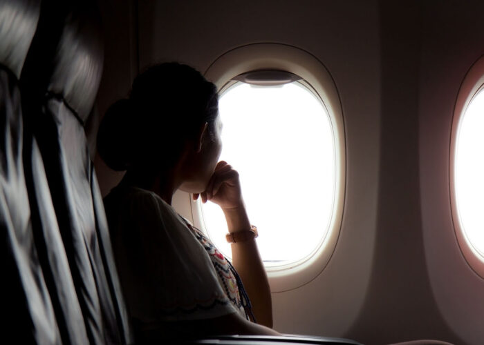 woman looking out airplane window.