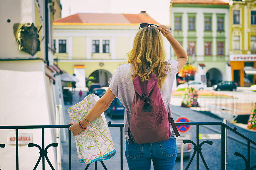 A young traveler with a map stands by the railing and looks at the historic city.
