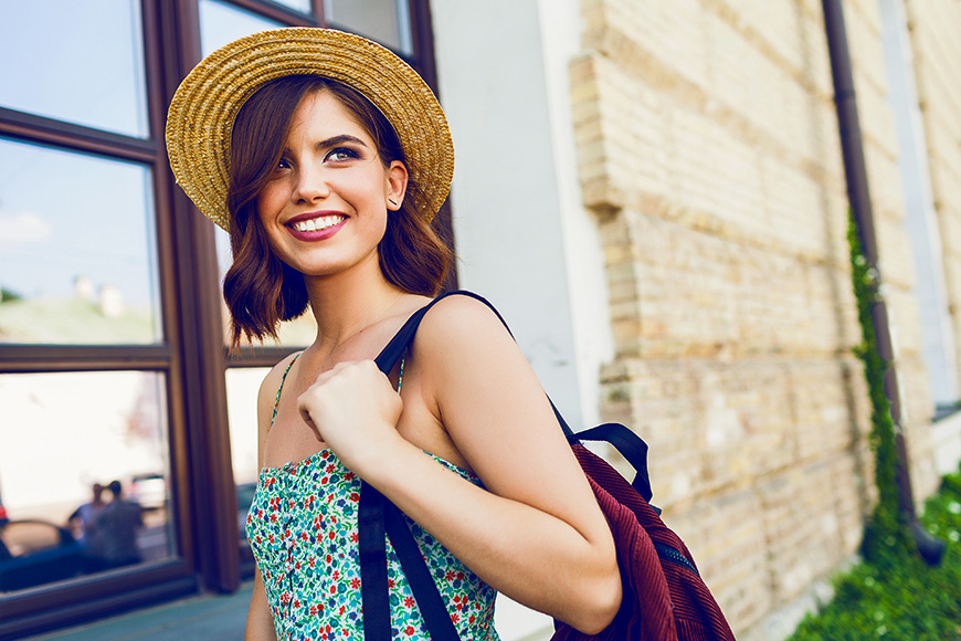 portrait of young stylish hipster woman walking on the street, wearing trendy outfit, straw hat, travel with backpack