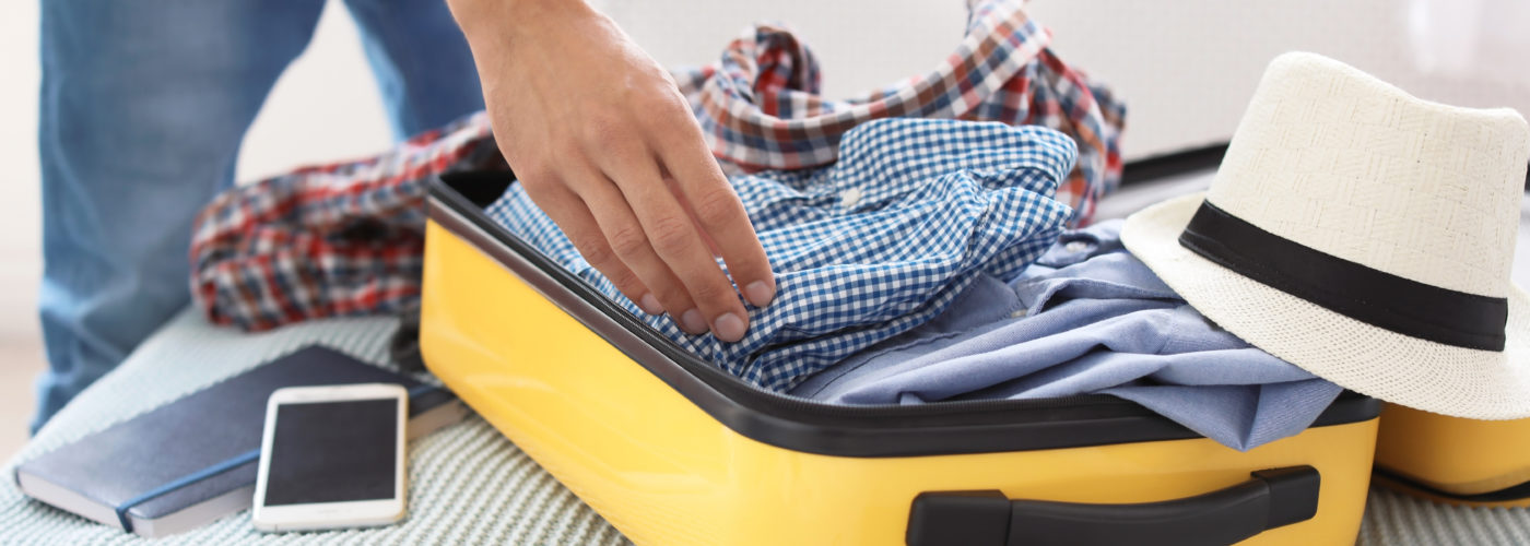 Person packing a yellow suitcase