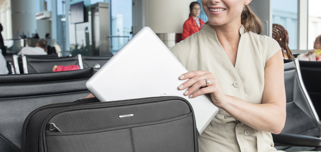 woman taking laptop out of suitcase