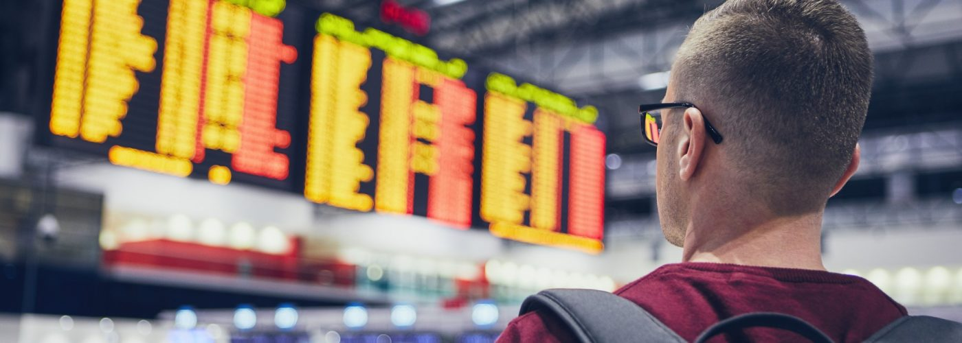 man looking at flight delay-prone airport board.