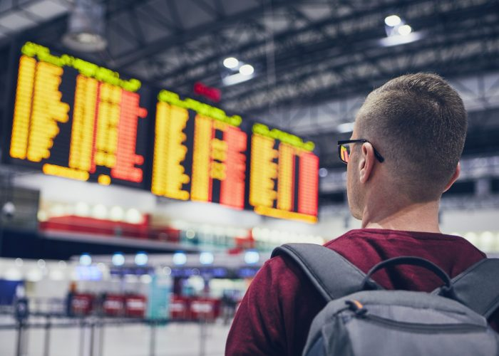 man looking at flight delay-prone airport board.
