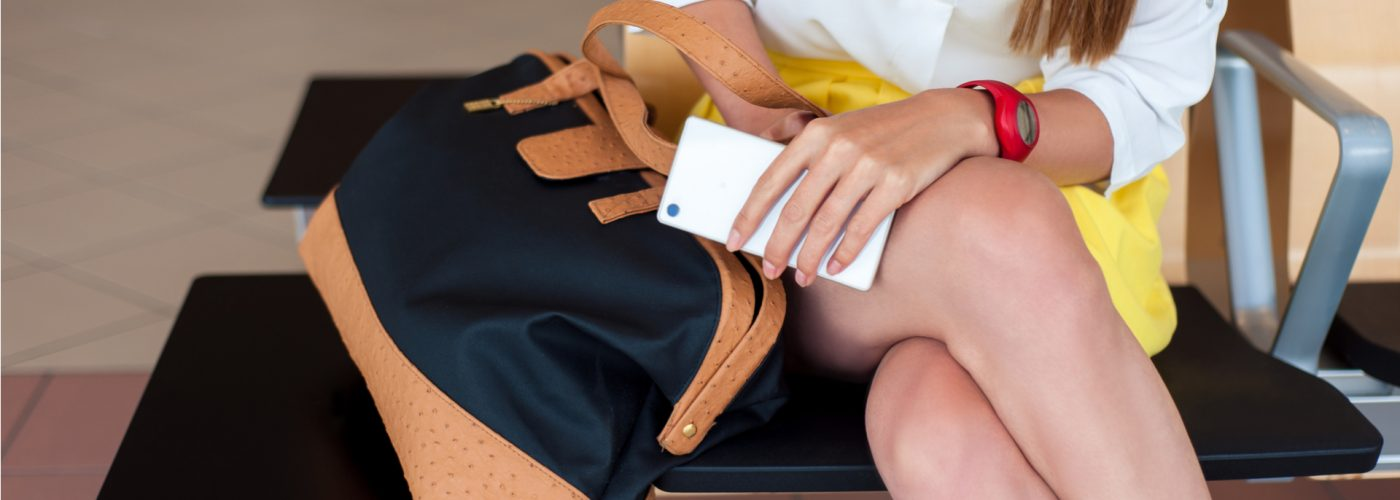 woman sitting at airport with bag