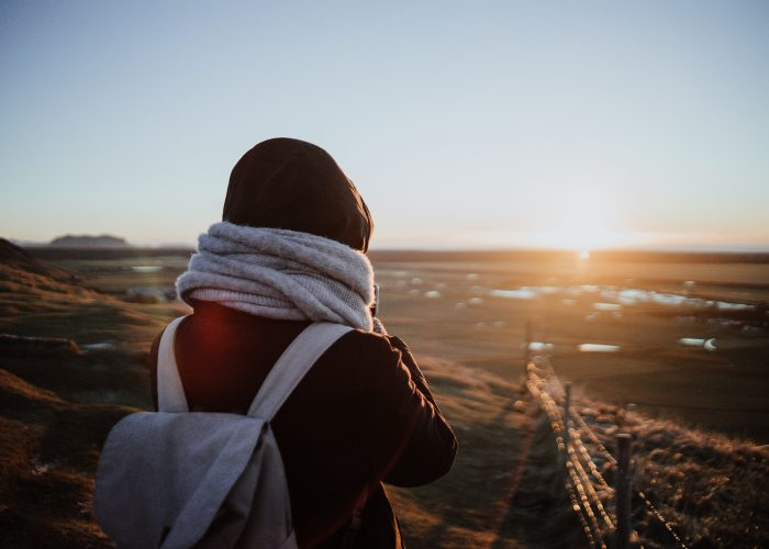 traveler with scarf and backpack at sunset