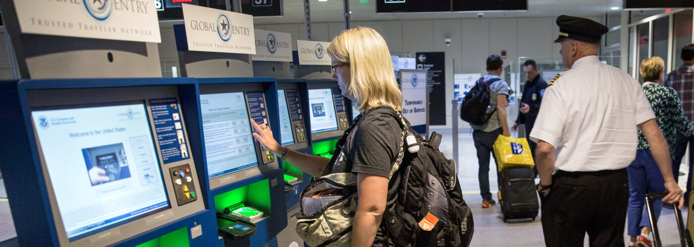 woman at global entry kiosk in Boston airport.