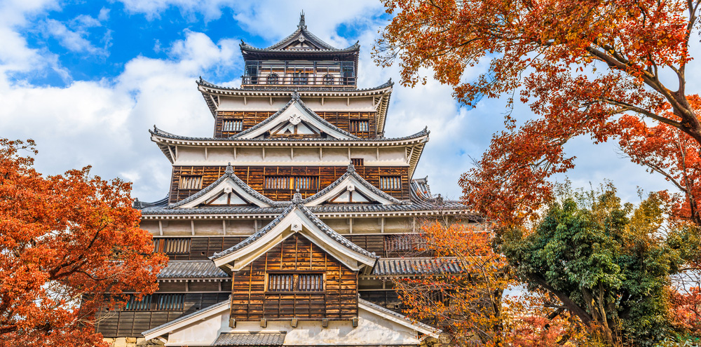 Tall japanese-style castle surrounded by trees showing autumn colors