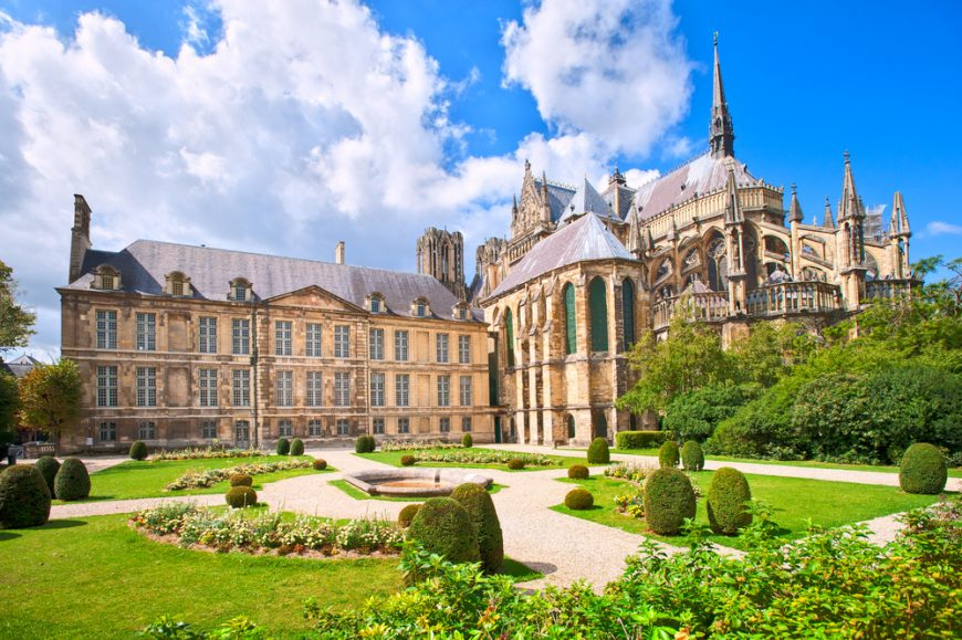 the back courtyard of the reims cathedral with lush green grass