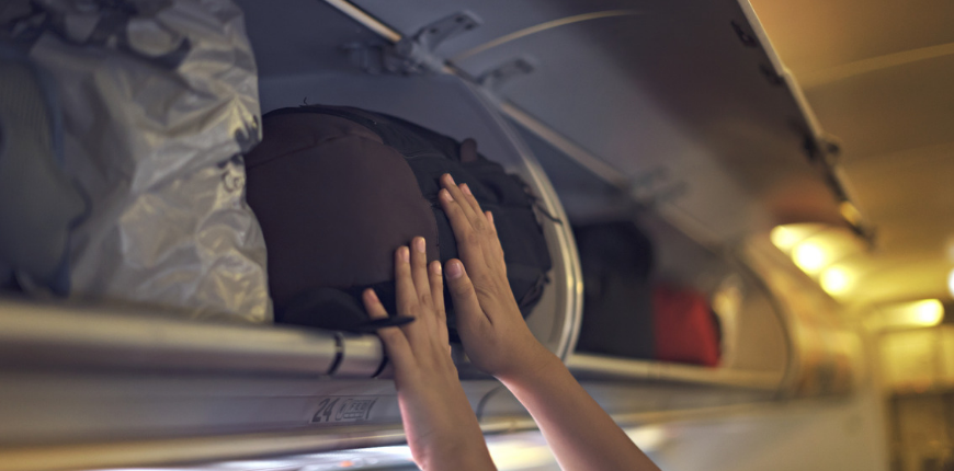 hands stuffing overhead bin on airplane