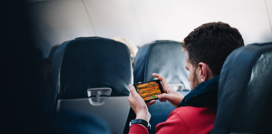 man playing game on airplane
