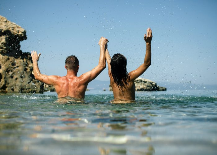 couple splashing water nude beach