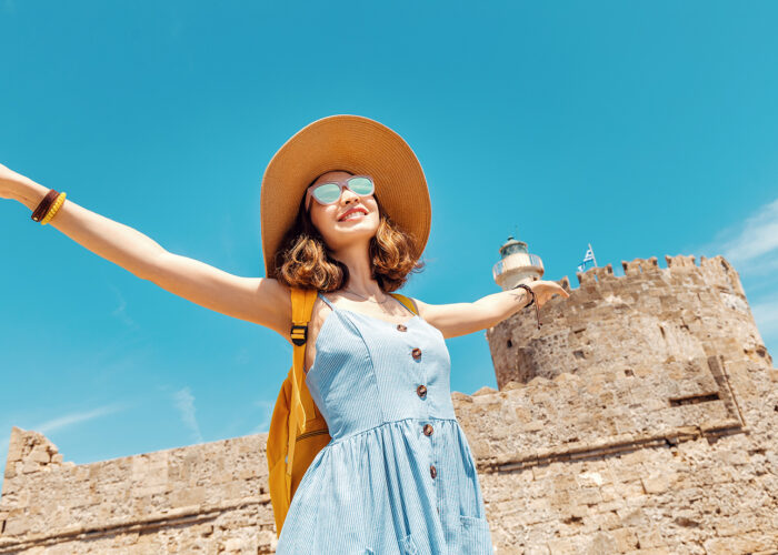 woman tourist arms out happy sunglasses sunny
