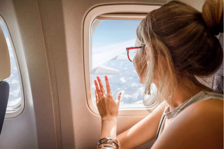 girl with glasses staring out plane window.