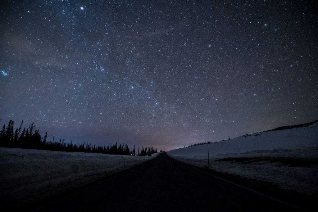 highway on dark road with bright sky stars
