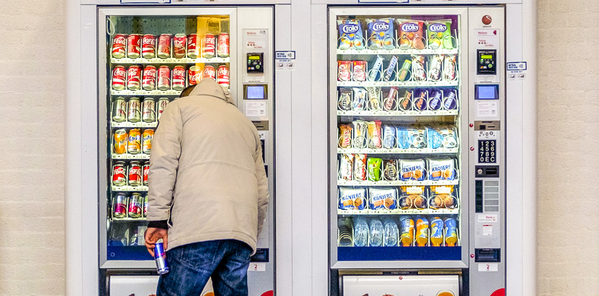 man purchasing soft drink vending machine