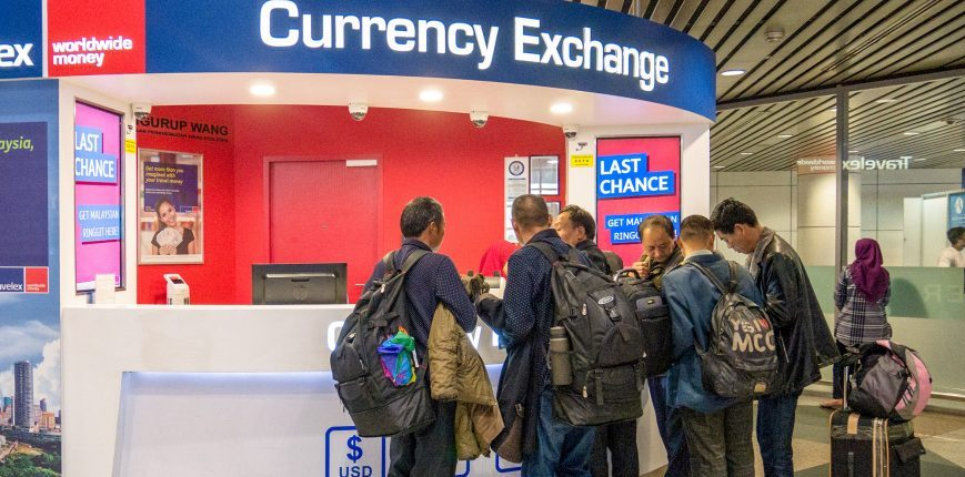 men exchanging money airport