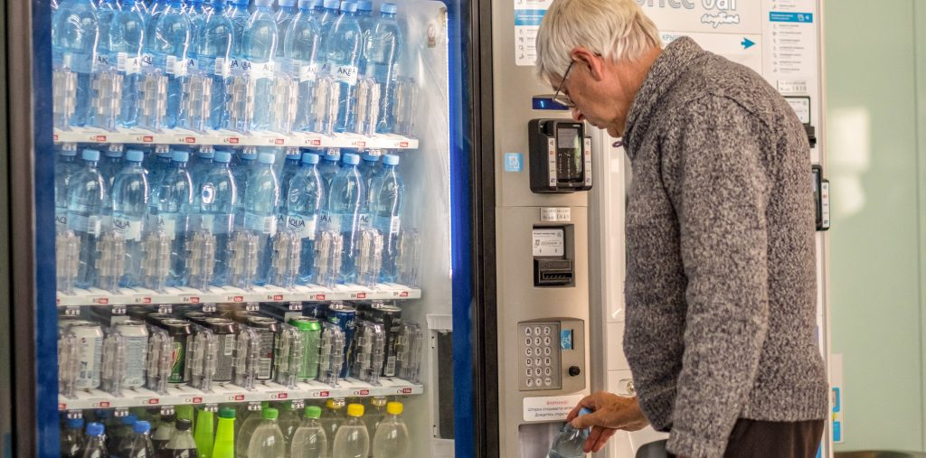 man purchasing bottled water from vending machine airport