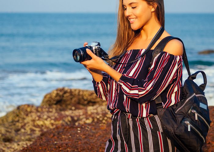 woman in jumpsuit with camera at beach.