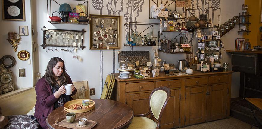 woman with mug at random tearoom and curiosity shop.