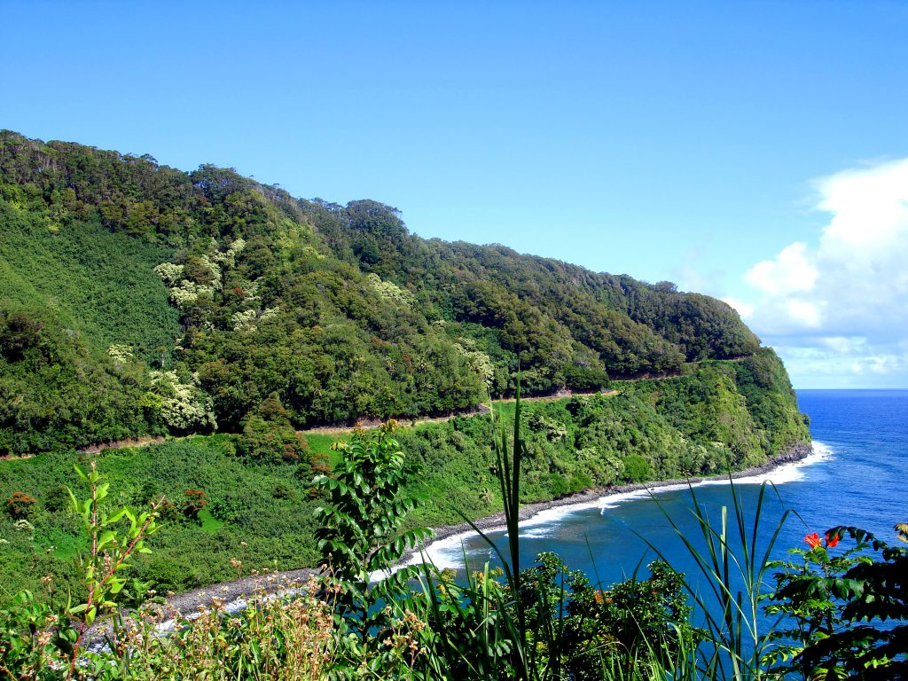 road to hana view of cliffside highway and ocean with green lush mountains lanscape