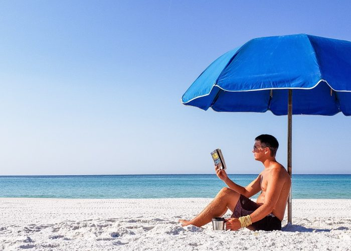 Man reading a paperback book under a beach umbrella.