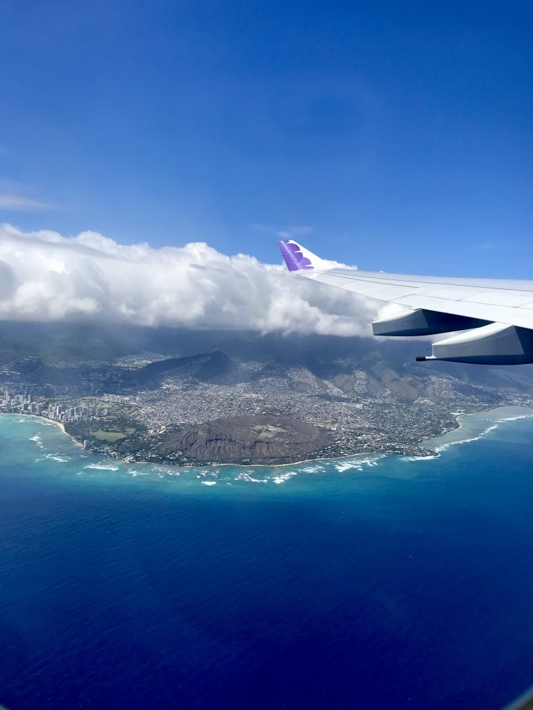 hawaiian airlines flying over diamond head crater and ocean.