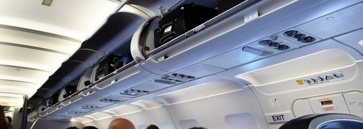 passengers on a plane with overhead bins open.
