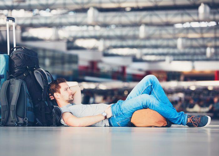 E.U. flight delays rule traveler waiting in airport.