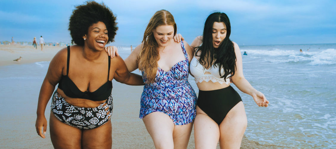 Three women walking through waves at the beach and laughing