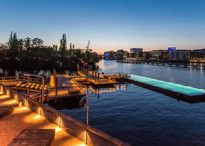 The Badeschiff pool in Berlin at night during a heat wave in Europe.