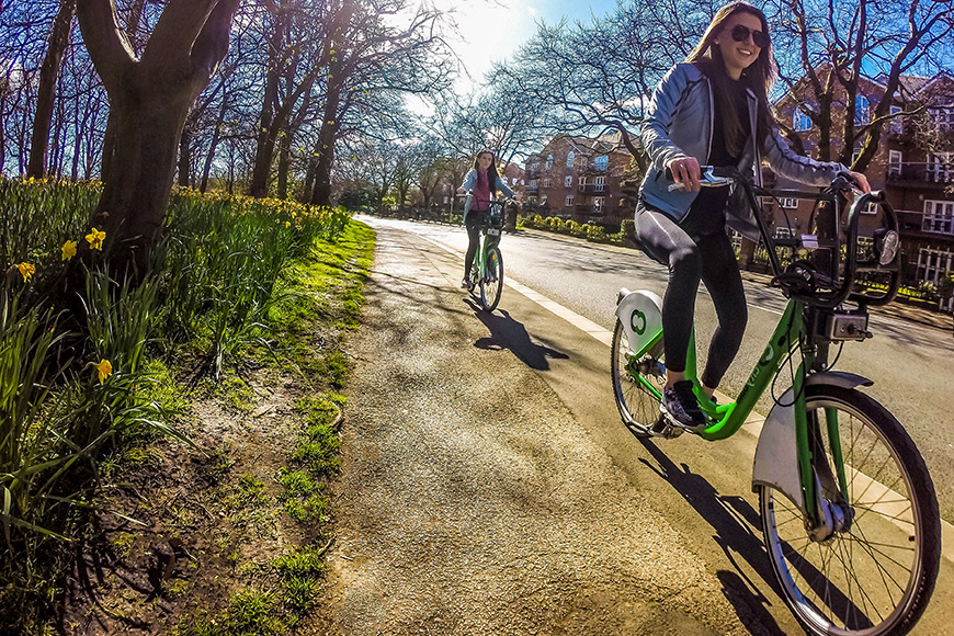 two women riding bicycles in city