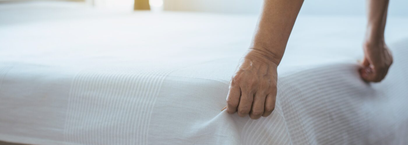 person making a bed in hotel.