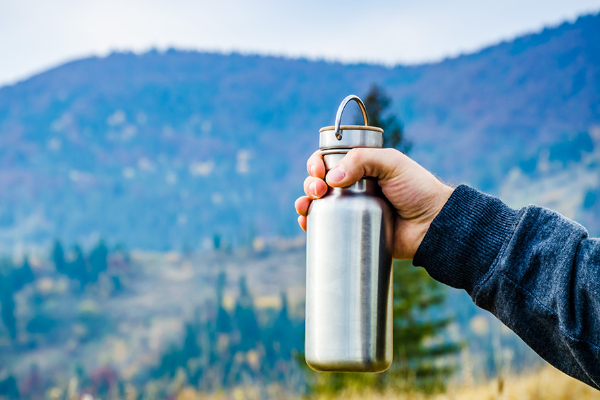 Man holding a bottle on the carpathian mountains background