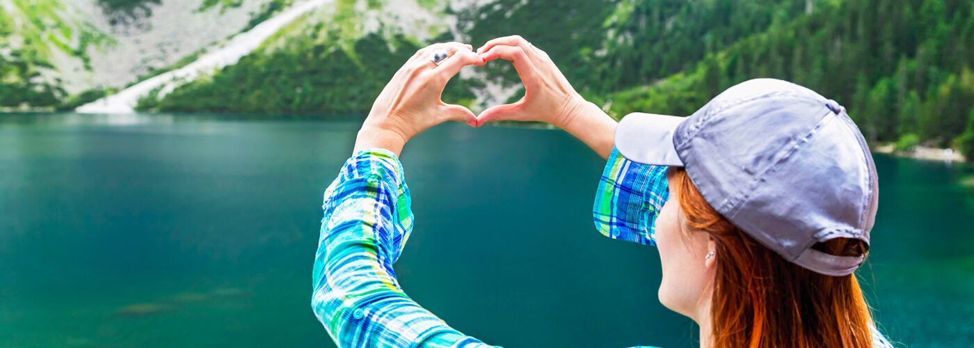 Girl make heart sign (shape of heart) on like, mountains background. In love with nature. Eye of the Sea lake (Morskie Oko). Tatra mountains. Poland.
