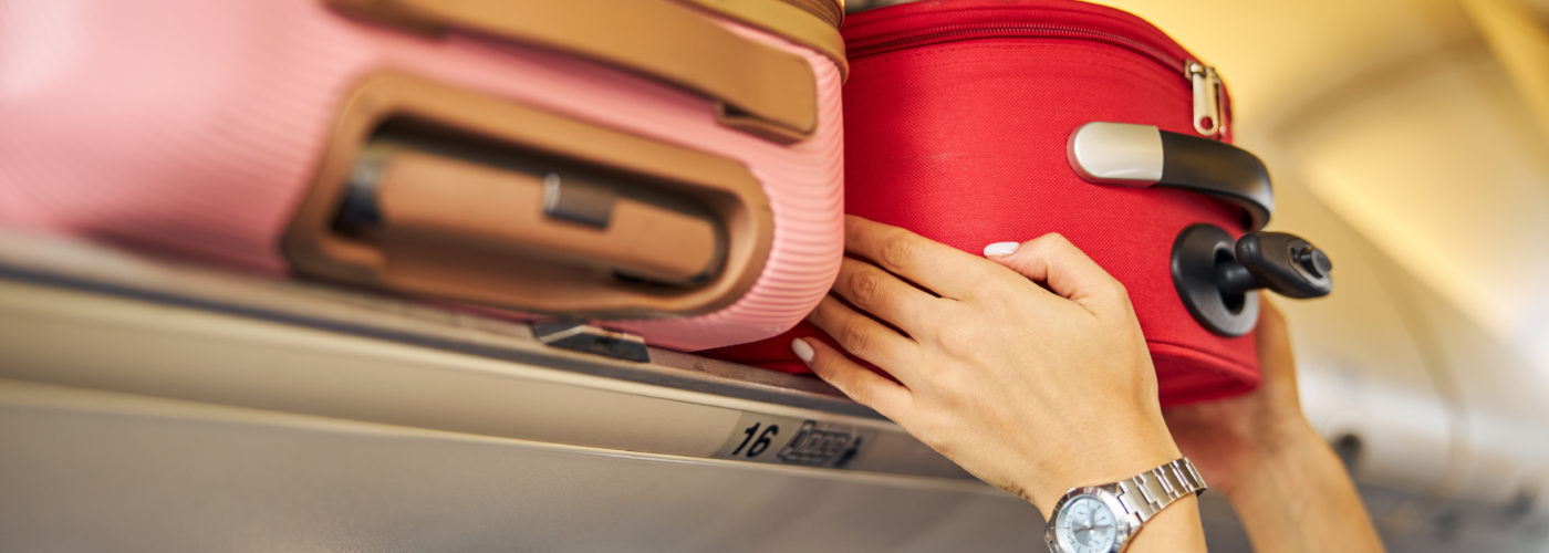 Person putting carry-on luggage in overhead bin