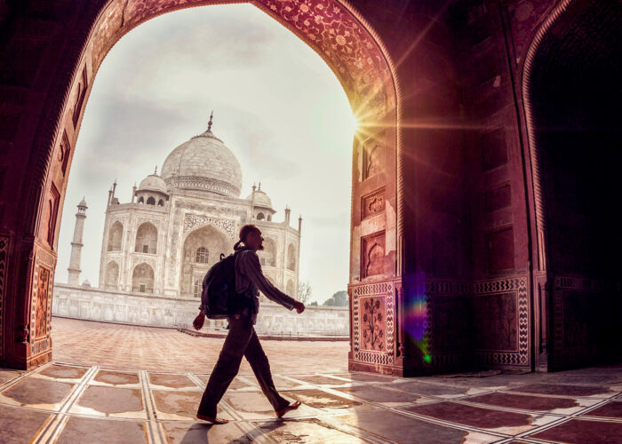 Tourist with backpack walking in the mosque arch near Taj Mahal in Agra