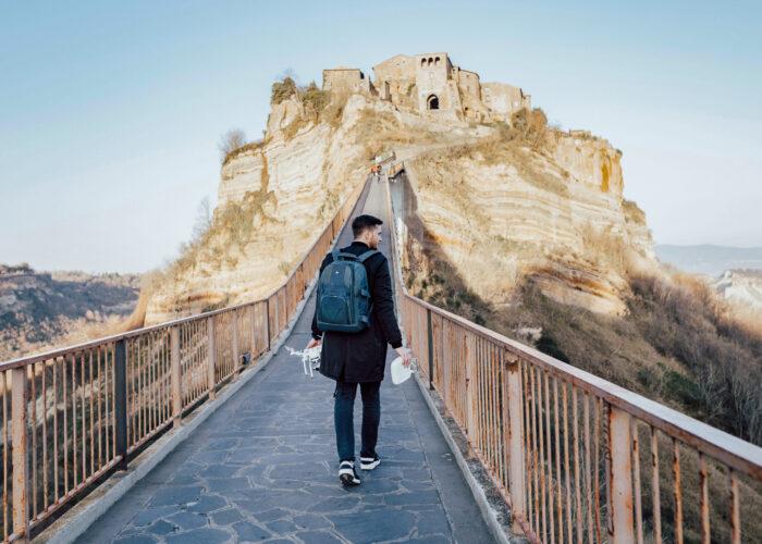 man walking up mountain wearing backpack