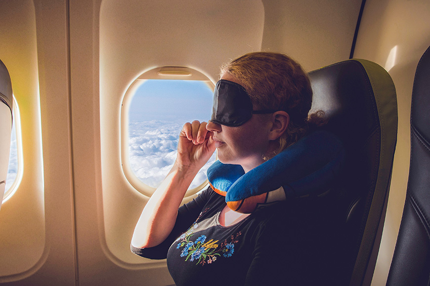 woman using travel pillow and sleeping mask in plane.
