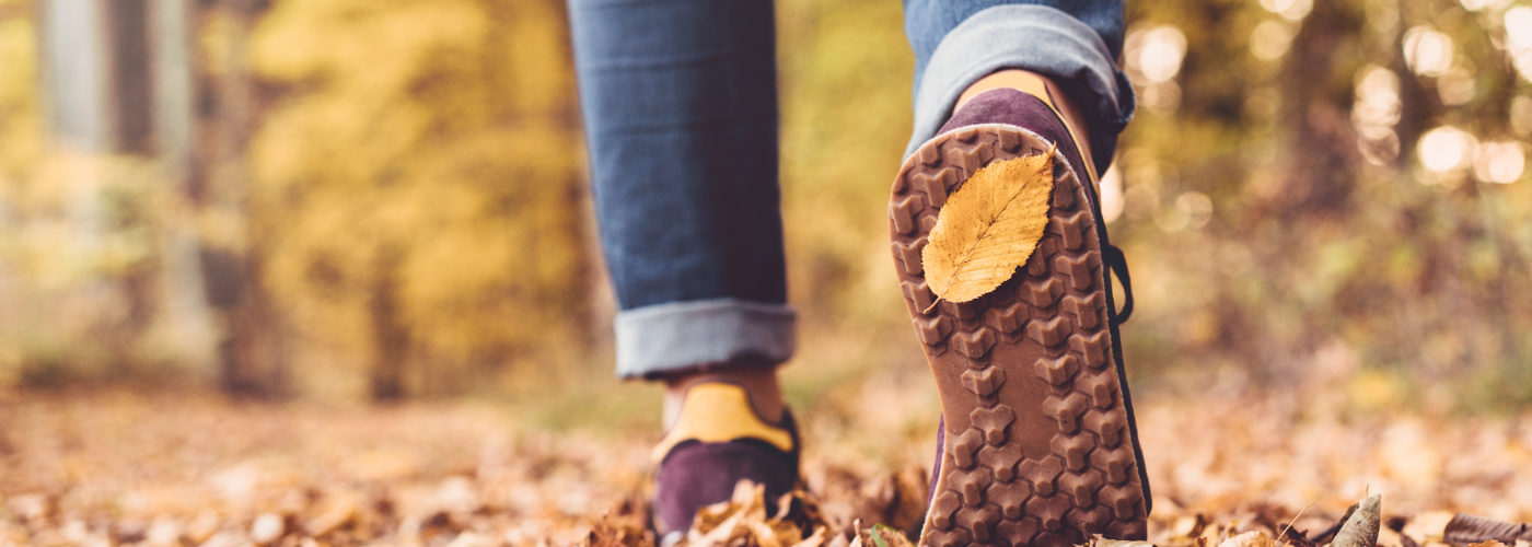 Close up of feet walking away from camera in a fall forest