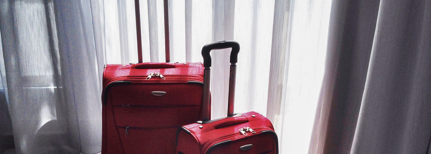 two pieces of luggage by window
