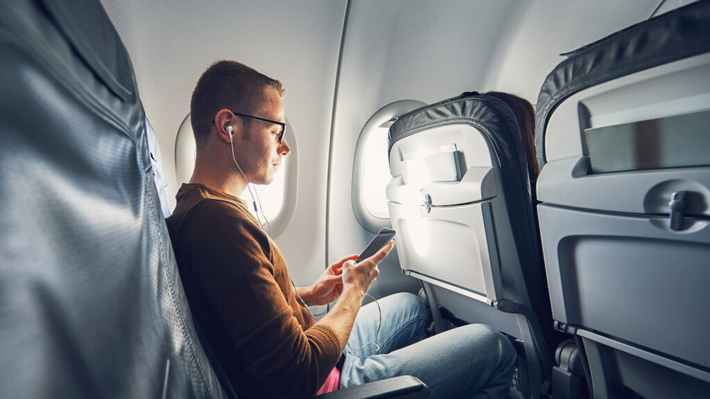 man sitting on airplane headphones and phone