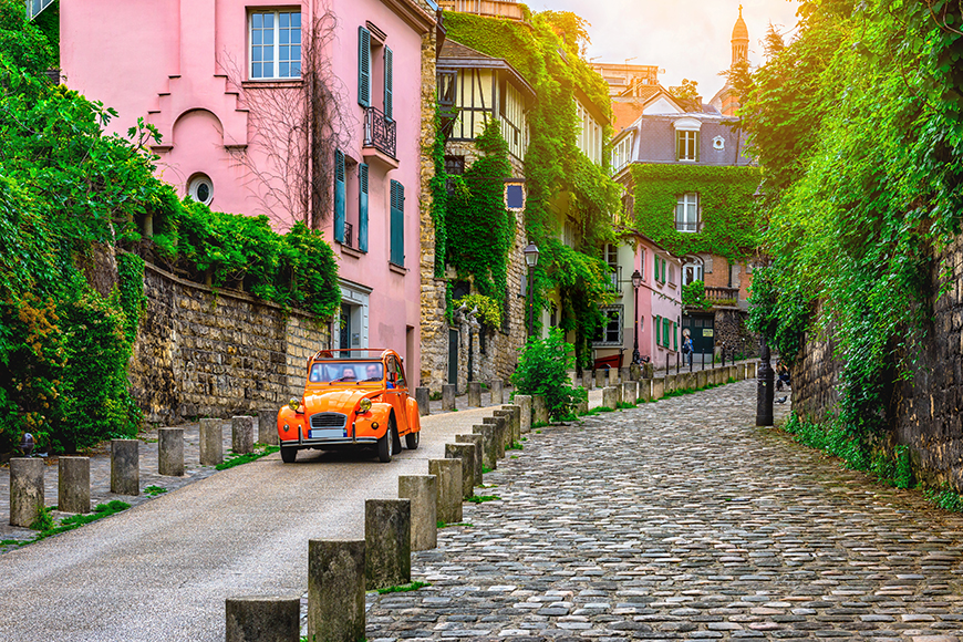 orange car on paris cobblestone street.