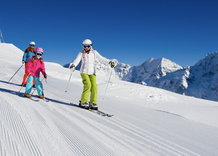 three people skiing down mountain