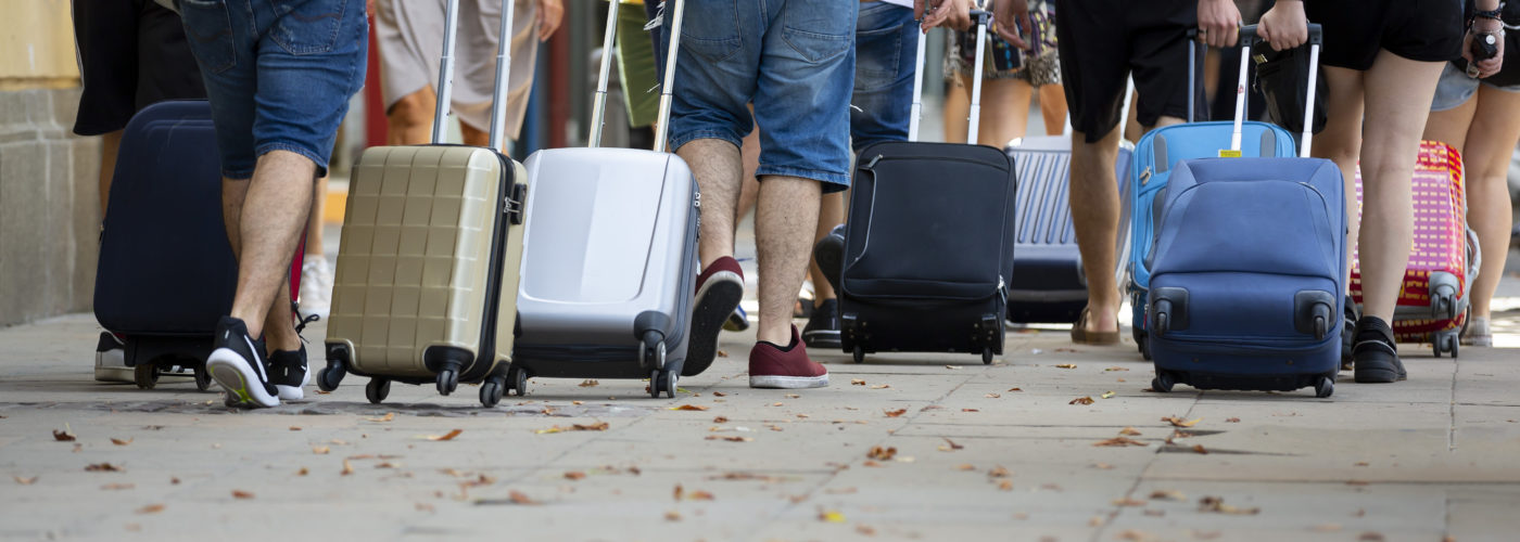 People pulling rolling suitcases in large crowd