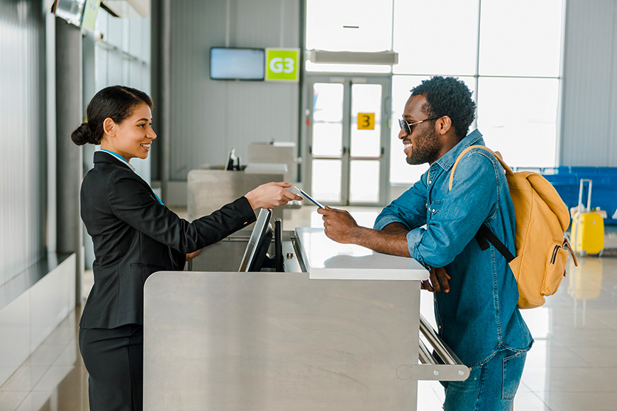smiling african american airport worker taking passport and air ticket from tourist with backpack