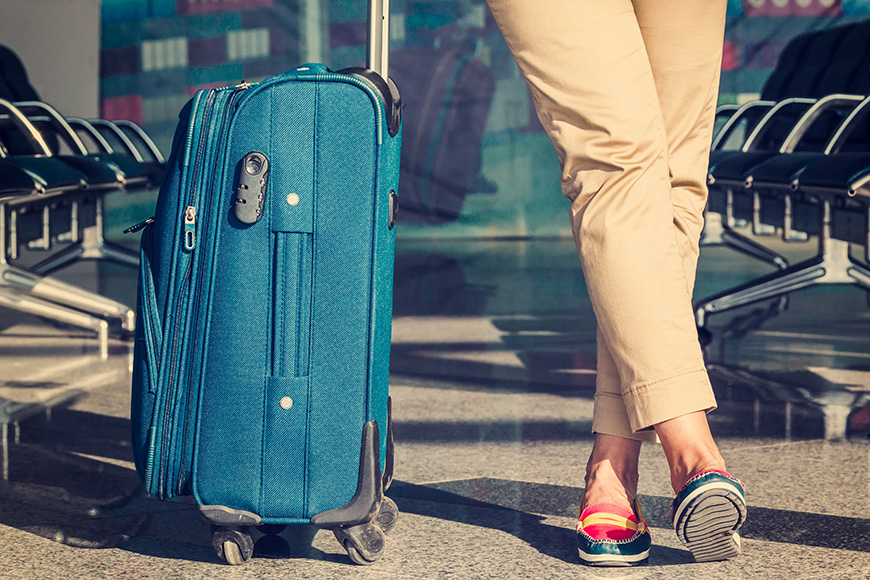 Legs of young woman close-up and blue baggage in airport