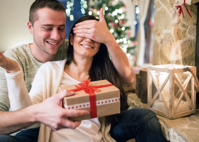 couple opening christmas gift fireplace