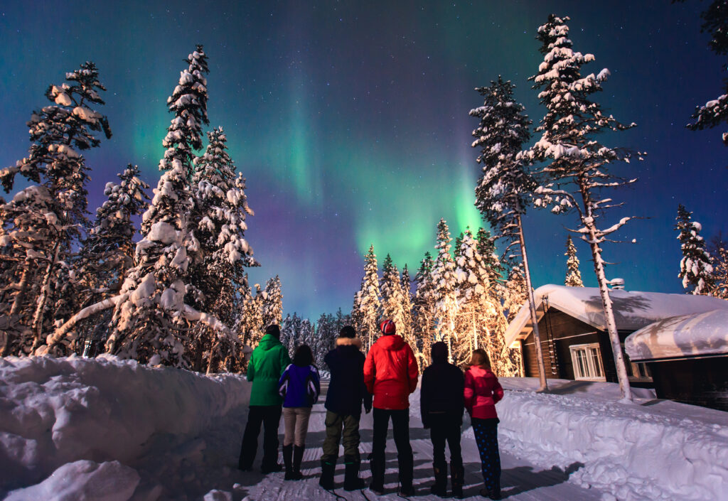 group of people viewing the northern lights in norway